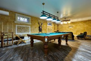 A fully finished billiards room in a basement with exterior waterproofing
