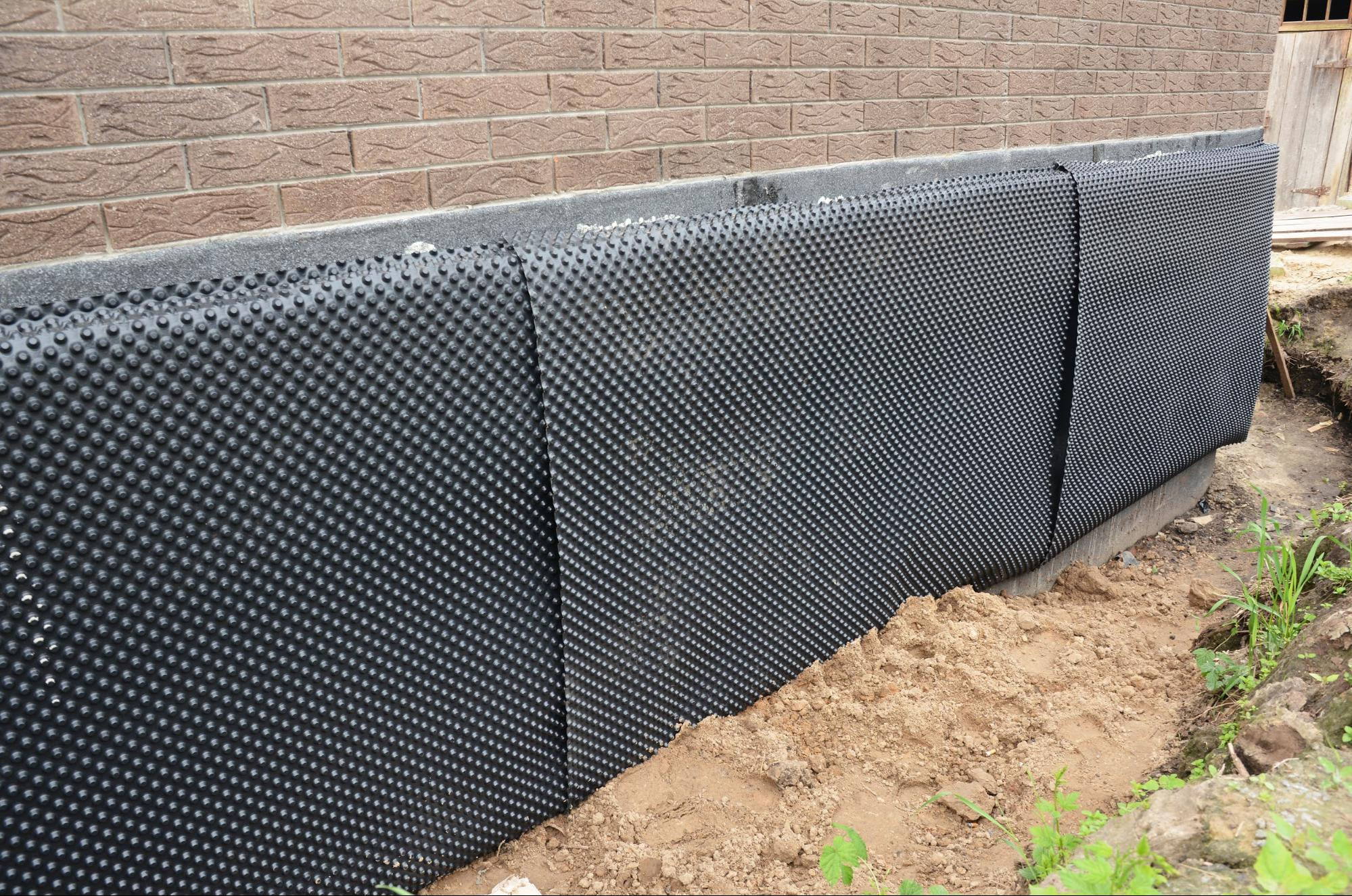 Outside view of exterior waterproofing done on a basement