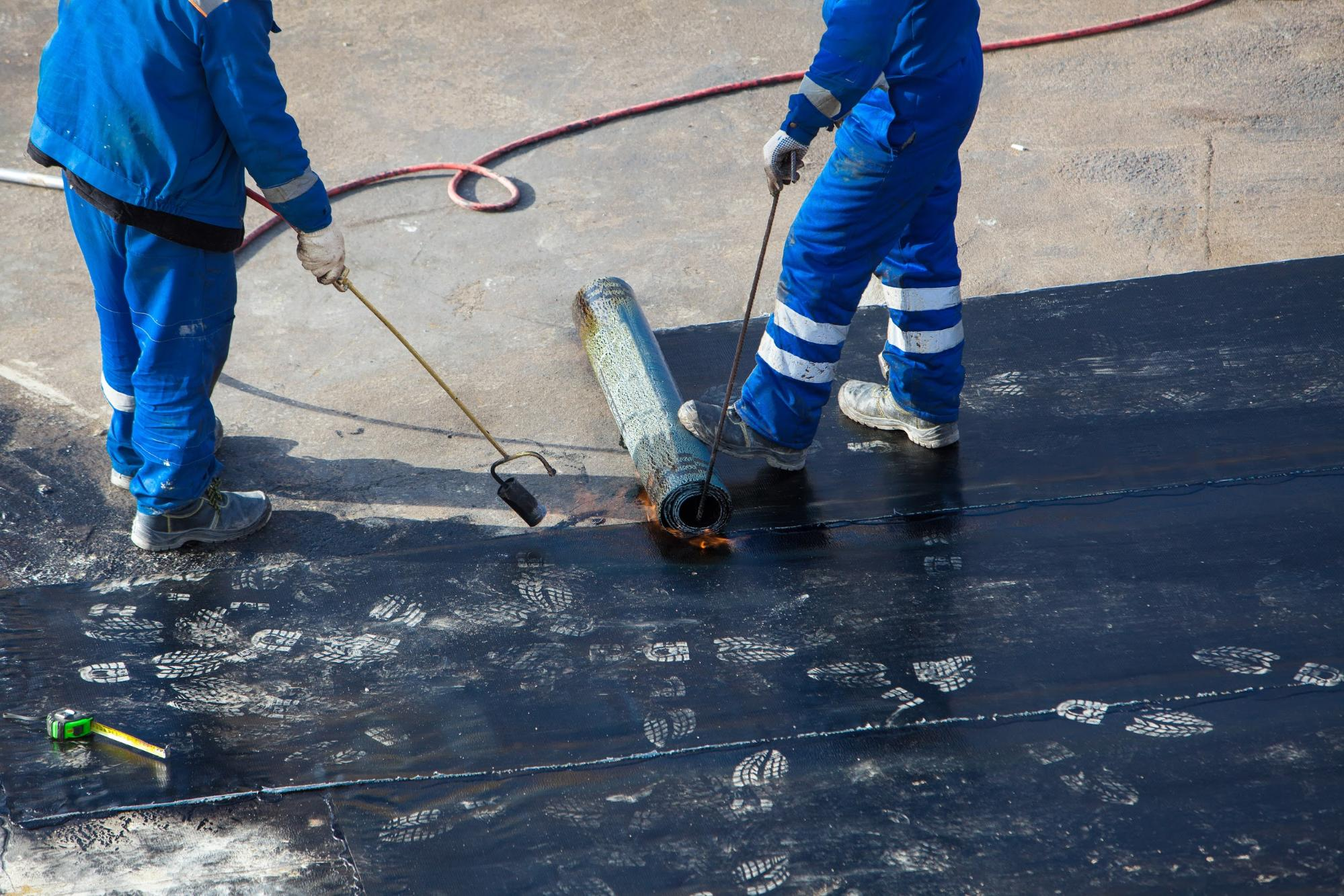 Professionals installing waterproof coating on concrete foundation